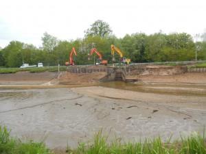 Dijkwerkers leggen een nieuw stuk damwand aan weerszijden van de inlaat, waar de oude dijk het begeven had.