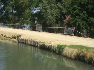 zo repareer je een dijkdoorbraak op z'n Frans. Tussen de bomen zie je de Garonne.